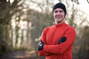 Portrait Of Man On Winter Run Through Woodland